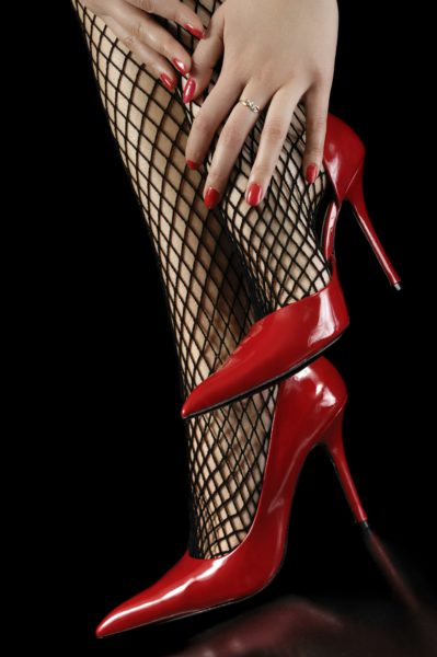 Sexy woman's legs in fishnet stockings and red shiny high-heel shoes