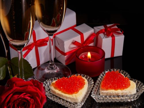Two wineglasses of champagne, gift boxes, red rose and two canapes with red caviar in the shape of a heart standing on a black background. Valentine's day