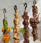 Cooked Chicken, beef and vegetable kebab skewers hanging from a rack, served with fries, and ready to eat.